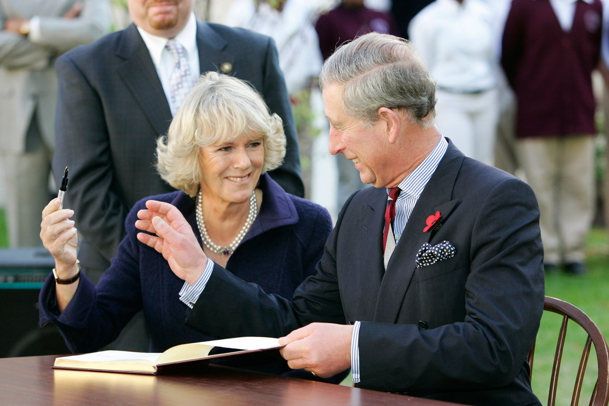 TRH Prince Charles, Prince of Wales and Camilla, Duchess of Cornwall giggle as she is reluctant to return his pen as they sign the visitors' book at SEED School.