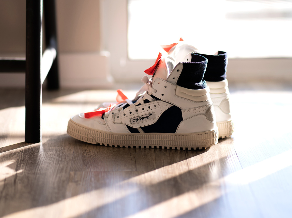 Off-white sneakers rest near a screen door