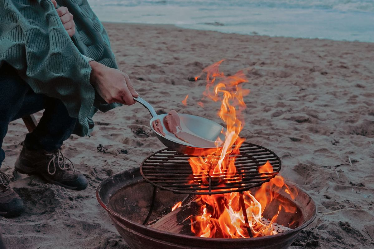 Camper cooks bacon over an open fire on the beach in Tynemouth, United Kingdom