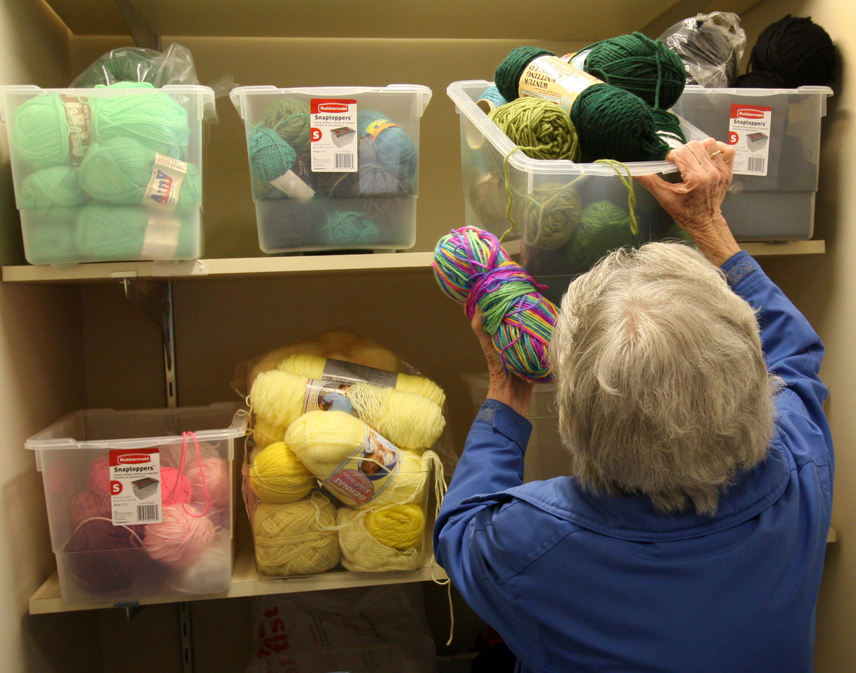 Woman stores yarn in plastic containers in a closet.