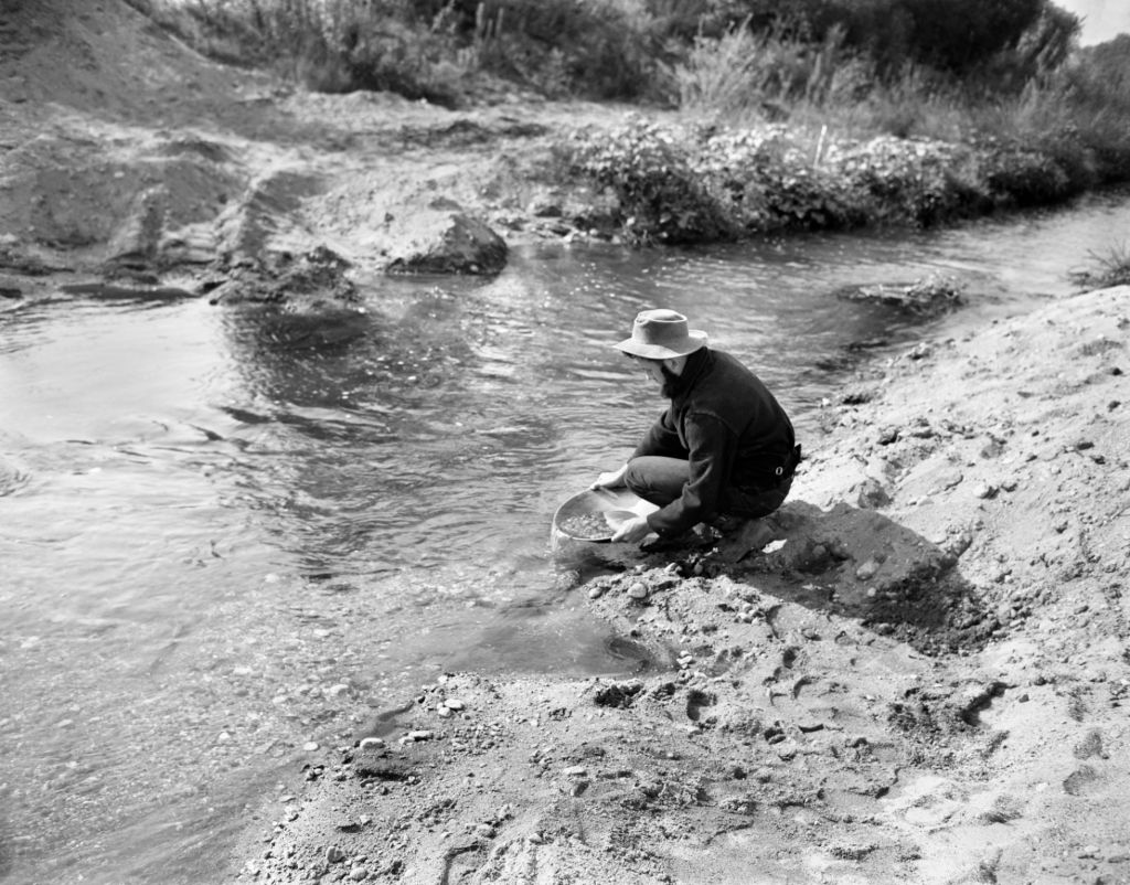 a person by a stream panning for gold