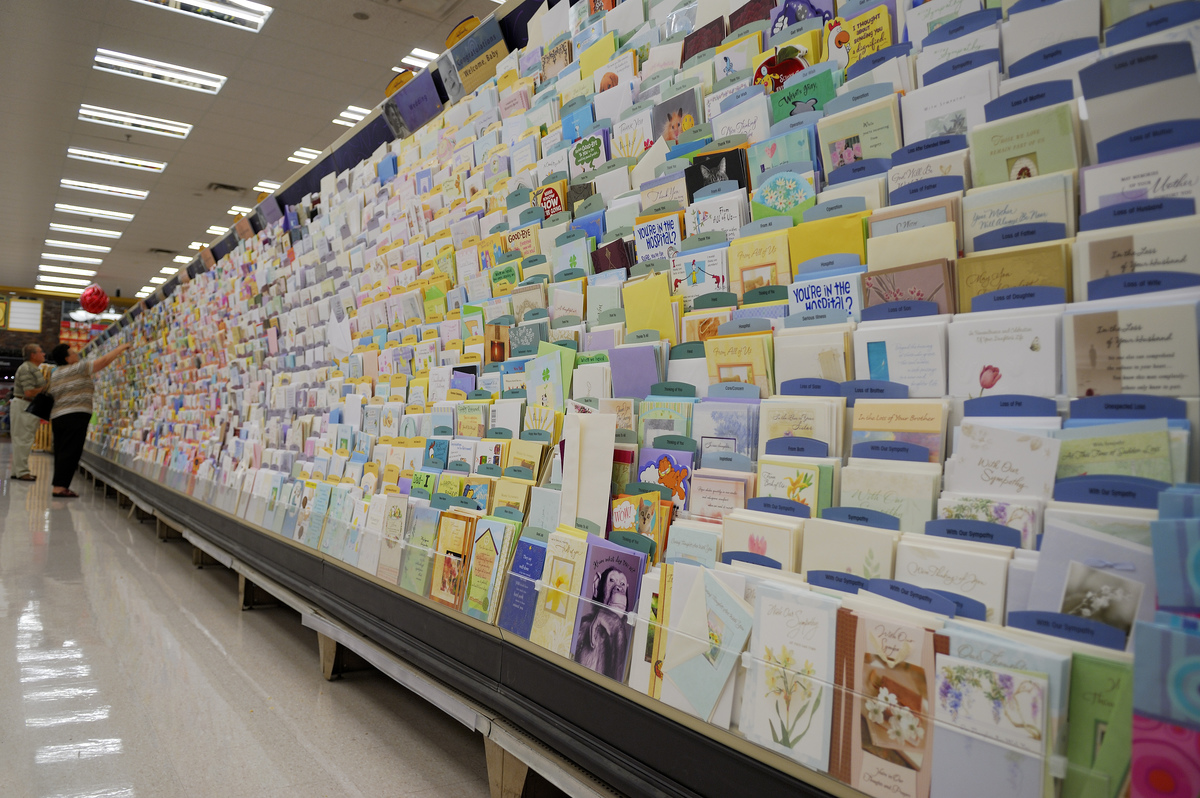 Elderly couple chooses a greeting card from a wall of options.