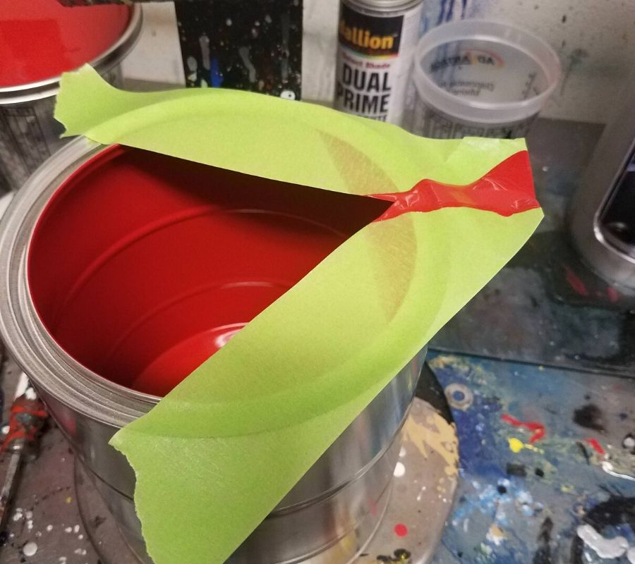 using tape to make a pour spout on a bucket of paint