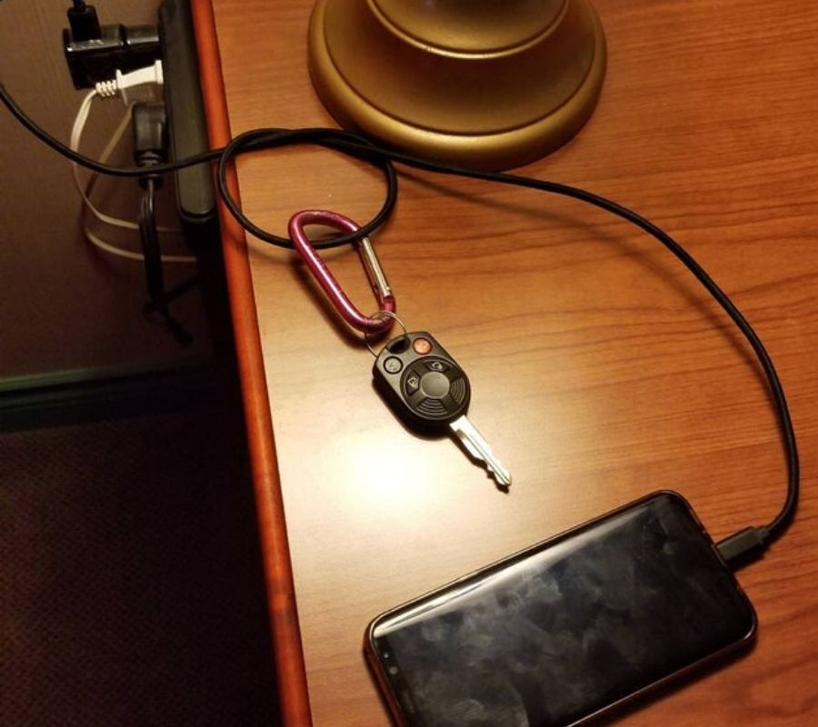 a charger tied in a loop and keys attached to it
