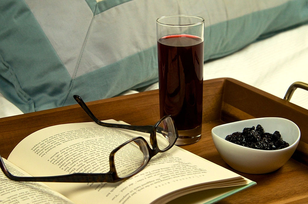 tart cherry juice, a book, glasses, and dried fruit on a bedside tray