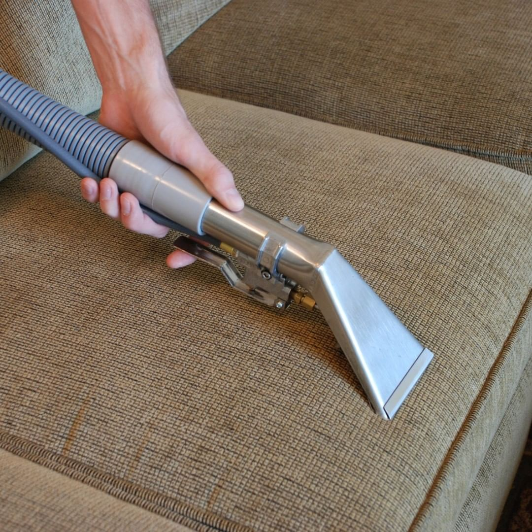 cleaning the couch with vacuum