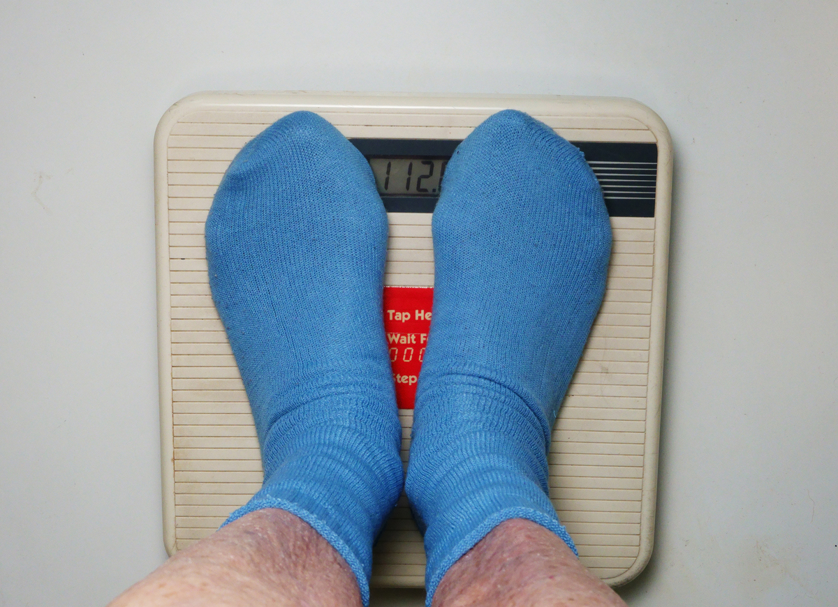 A person stands on a scale to weigh himself.