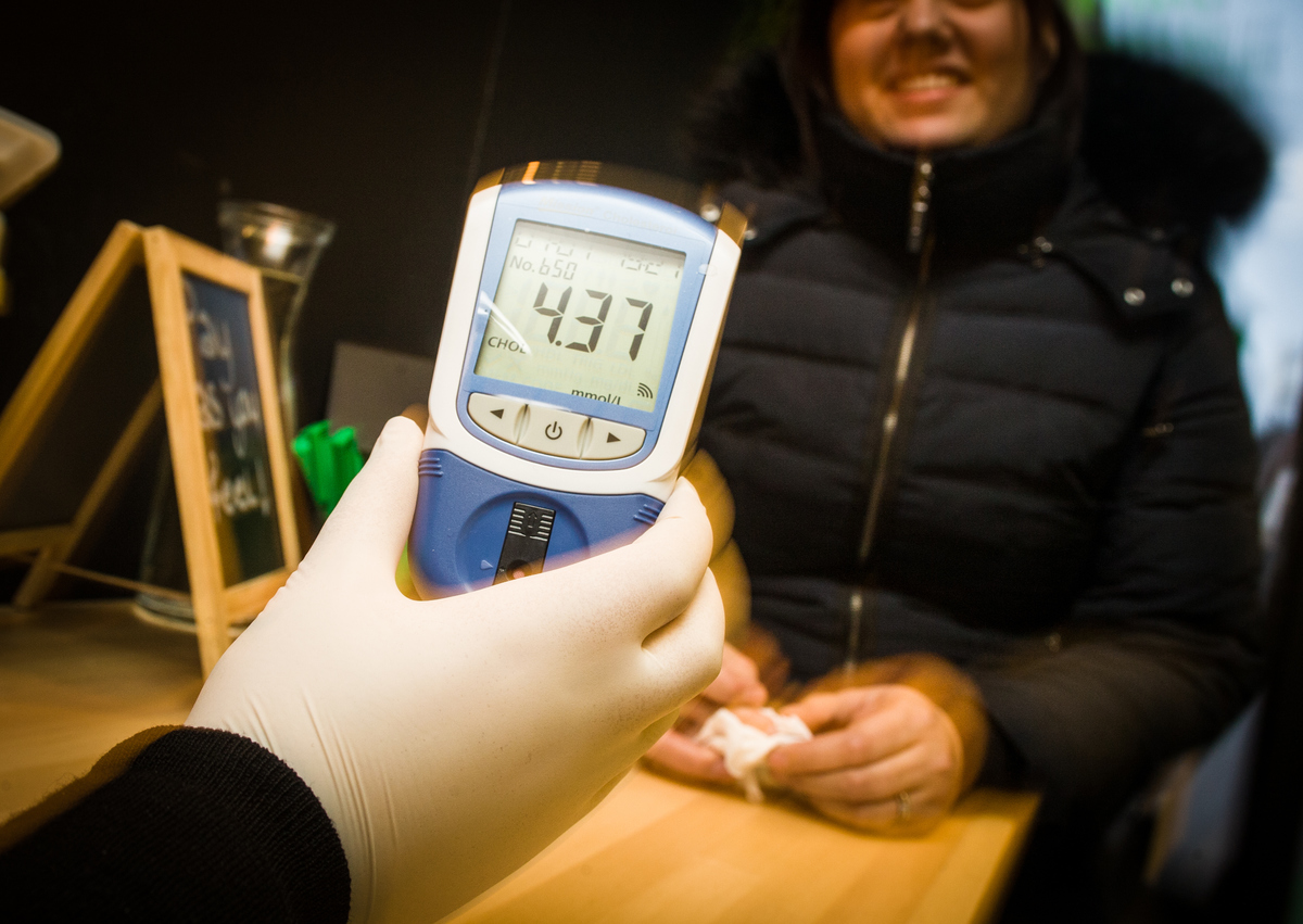 A man from the cholesterol foundation shows the result of a blood test for cholesterol screening.