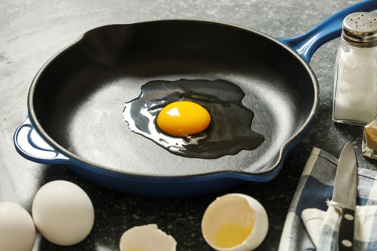 A raw egg is cracked in a frying pan.