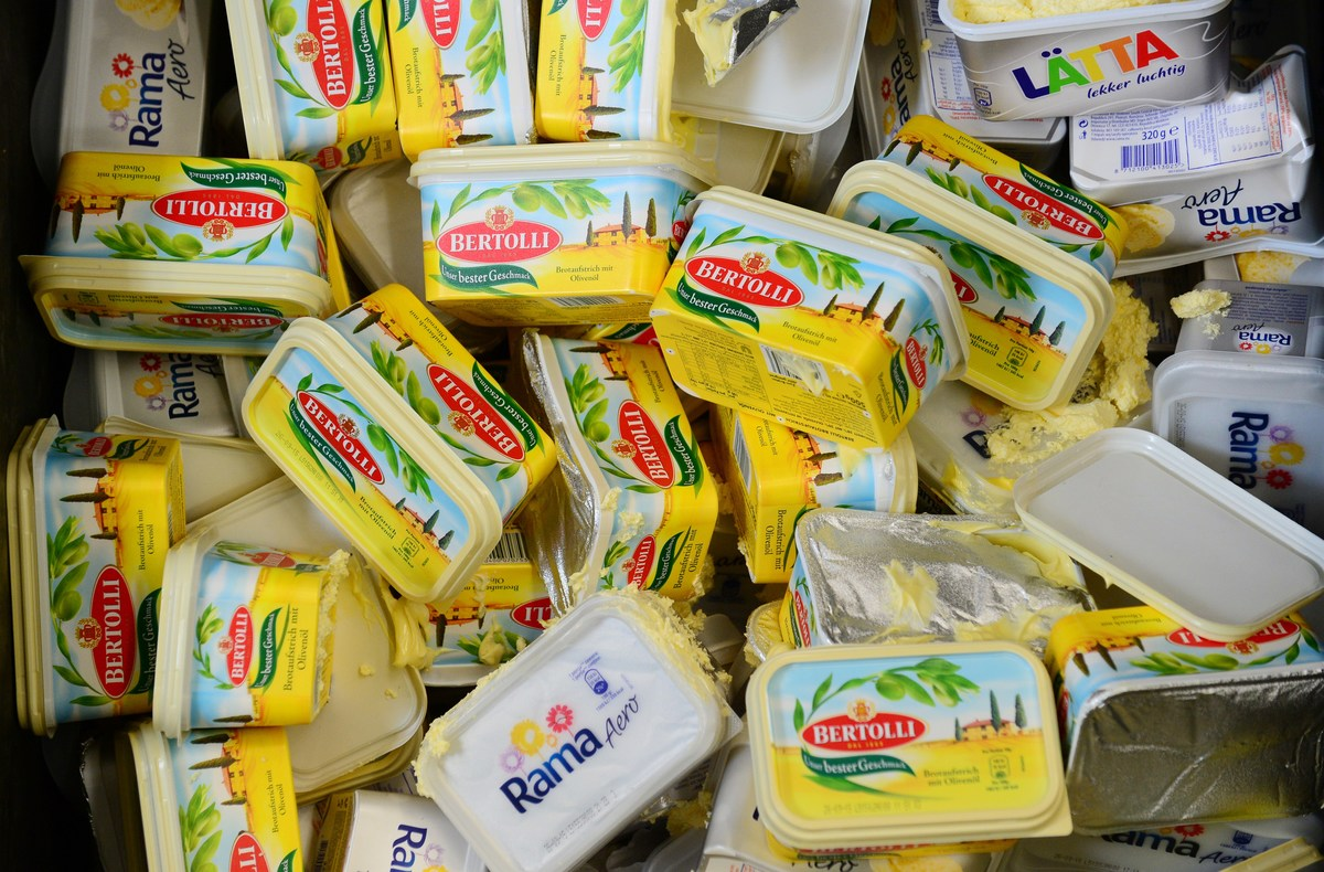 Margarine containers are piled in a trash can.