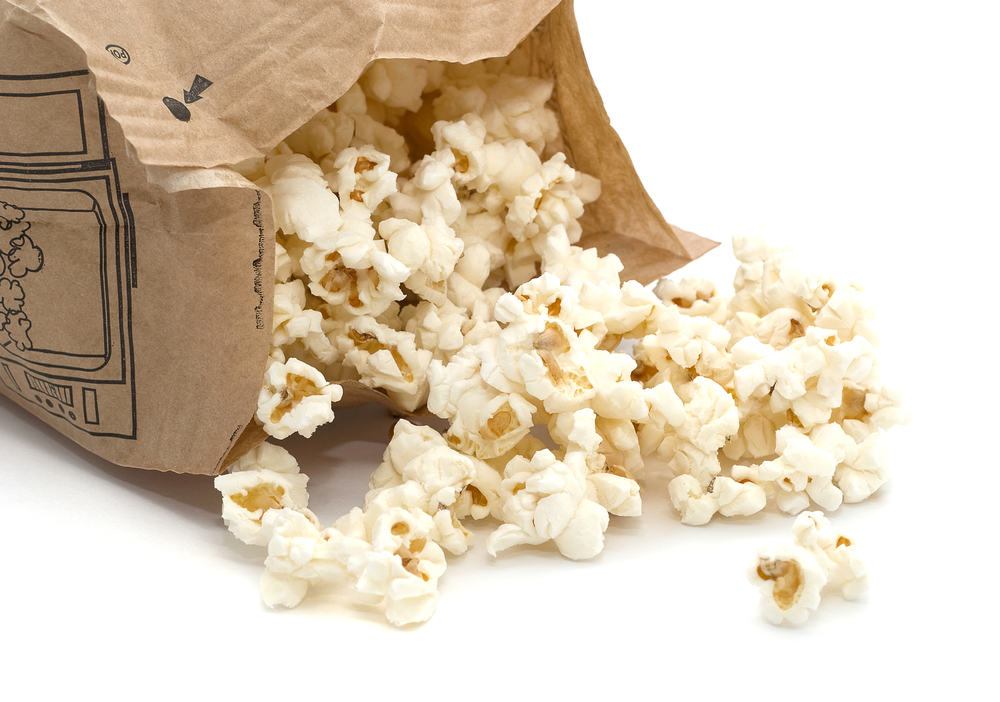 Popcorn pours out of a microwavable bag.