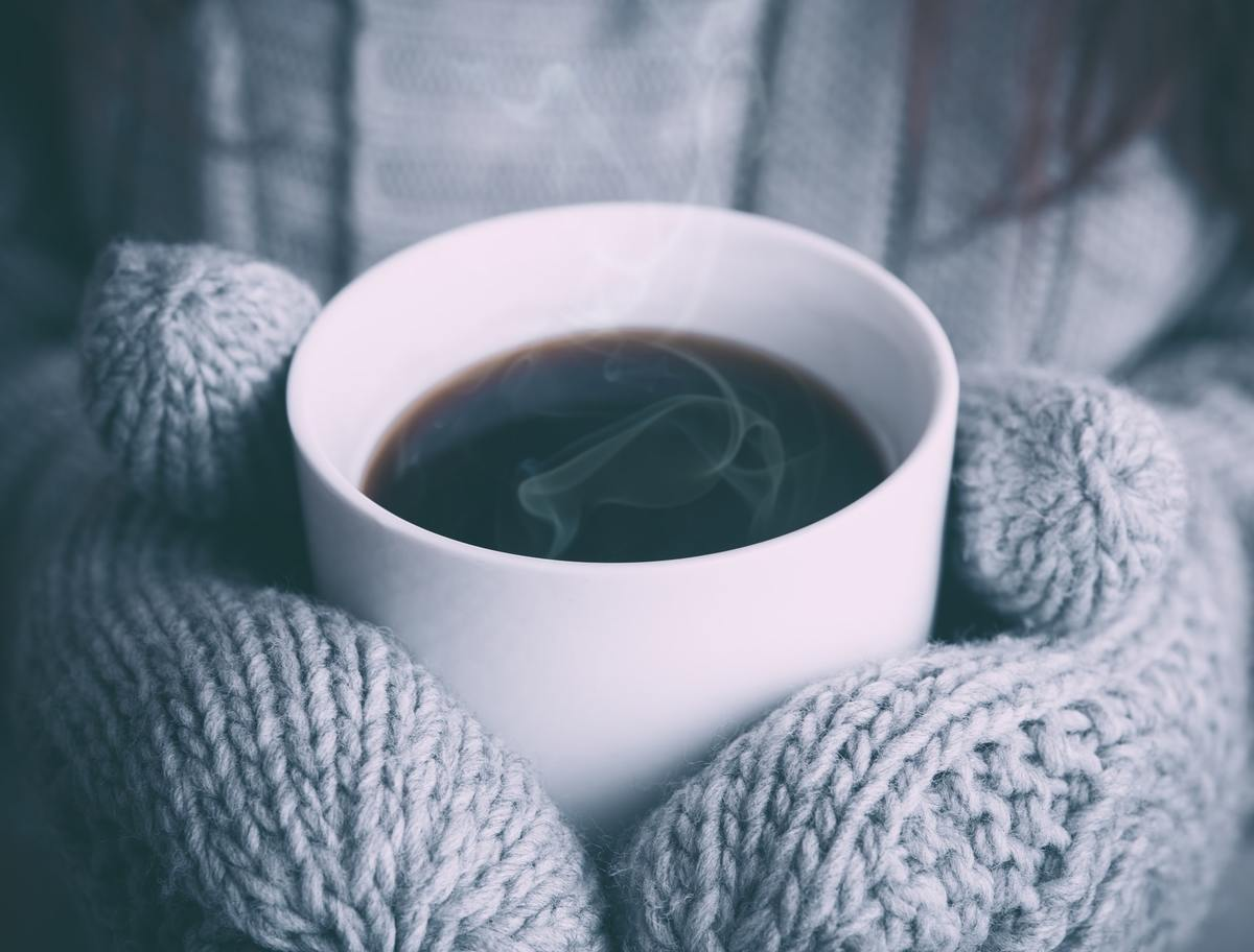 A person wearing mittens holds a cup of steaming black coffee.