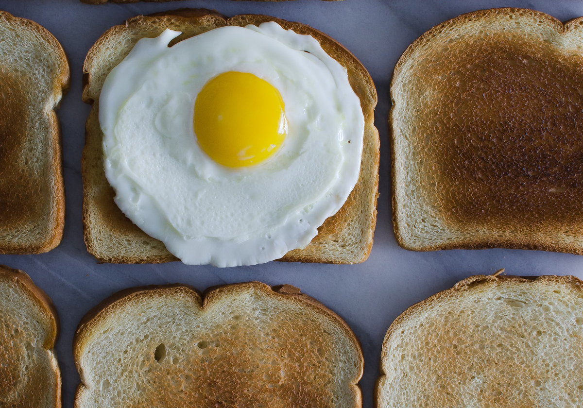 Toast is laid out, and an egg is on one.