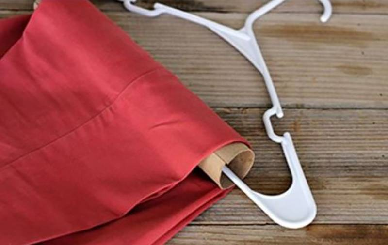 A toilet paper roll holds pants on a hanger.