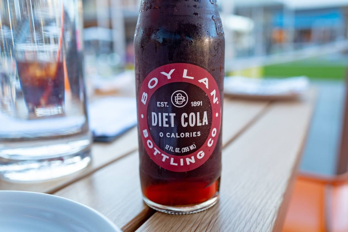 A bottle of diet cola sits on a restaurant table.