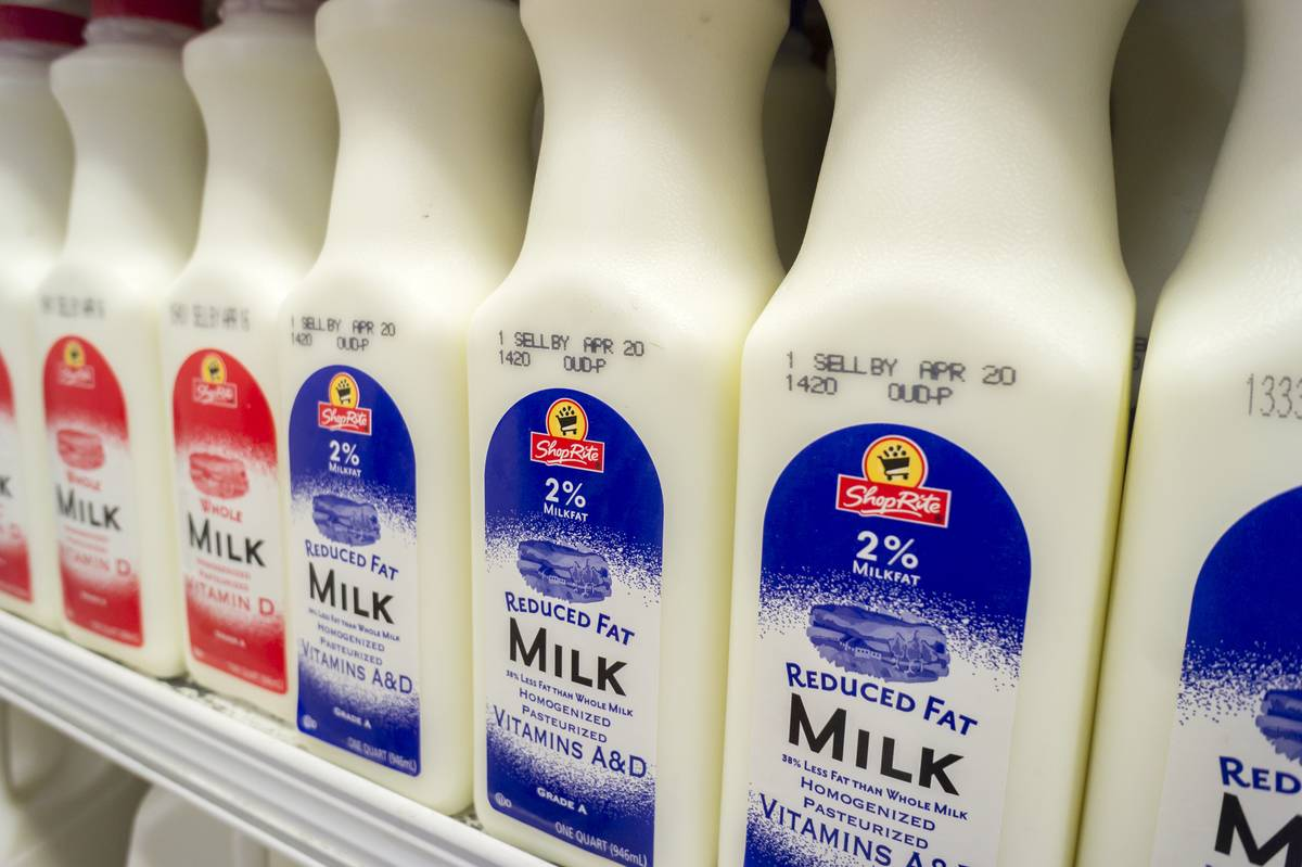 Reduced fat milk cartons are stacked on a grocery store shelf.
