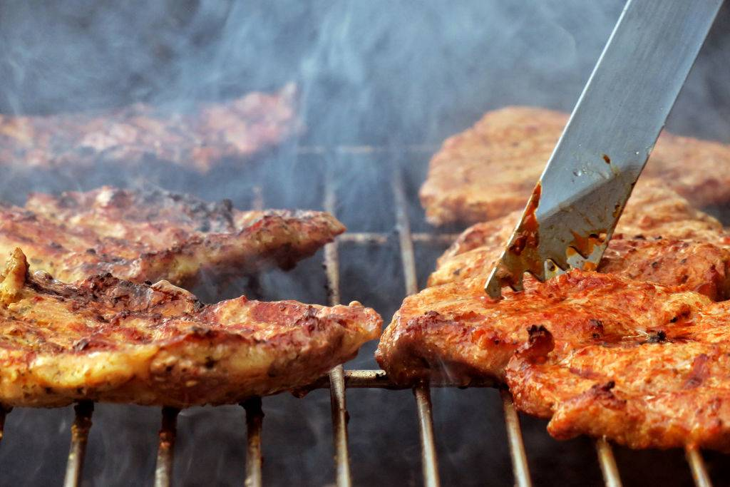 Steaks lie on a charcoal grill in a garden