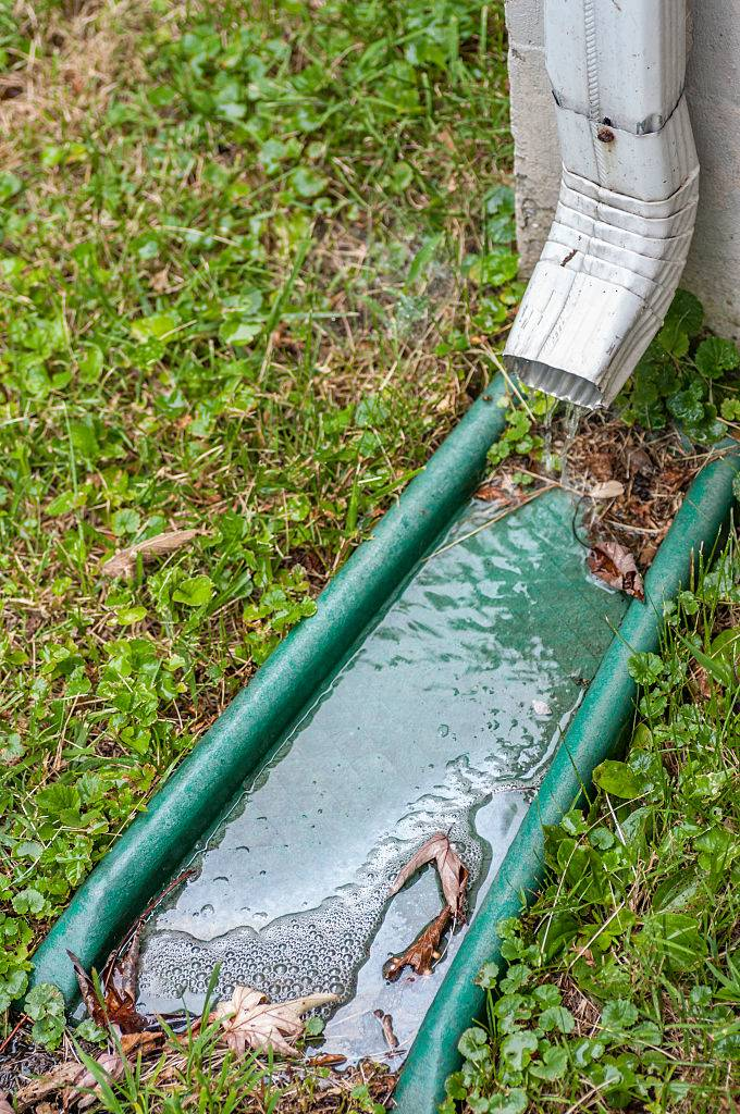 A pipe for carrying rainwater from a rain gutters called a downspout, waterspout, downpipe, drain spout, roof drain pipe, leader, or rone. At the end is a downspout silencer and a green splash block below..