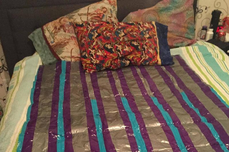 A DIY weighted blanket, made from rice and duct tape, sits on a bed.