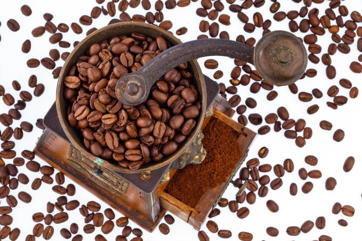 Coffee beans are in and around a grinder.