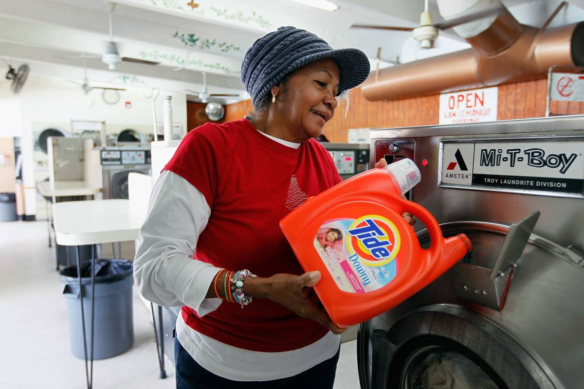 A woman pours laundry detergent into a washing