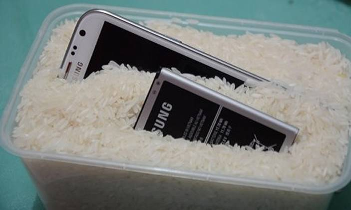Two Samsung phones are submerged in a container of rice.
