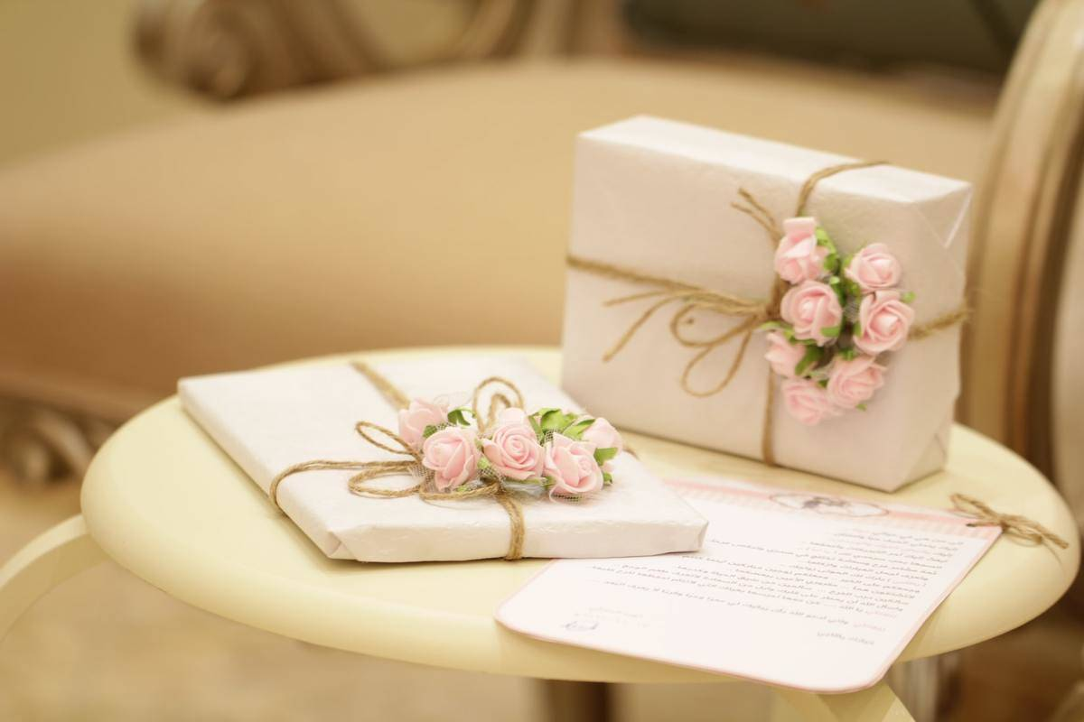 A wedding gift is wrapped with twine and pink flowers.