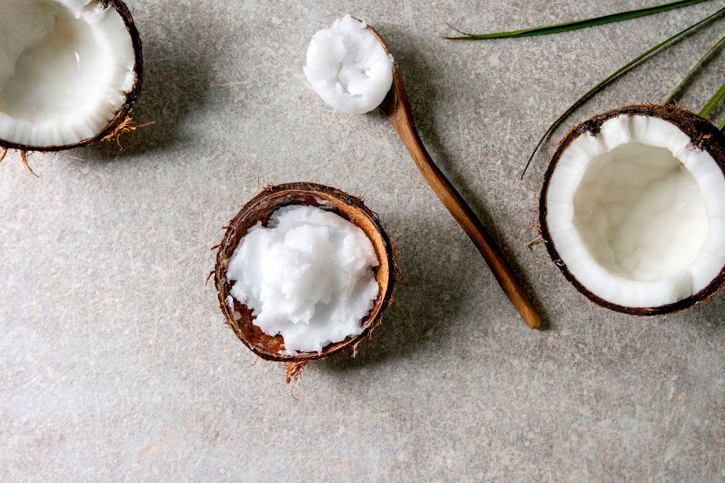 Organic vegan cold pressed coconut oil in coconut shell and wooden spoon over grey texture background