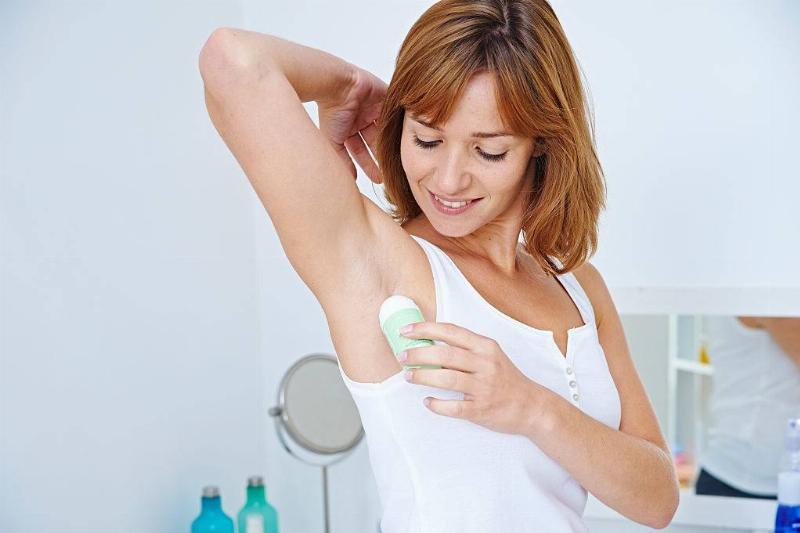 Woman applying roll-on deodorant