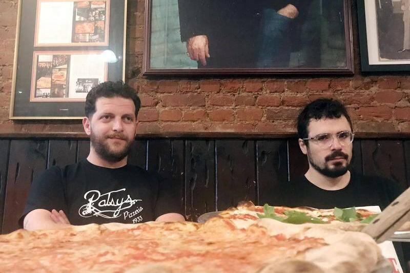 Armando Markaj sits next to another waiter in front of a pizza.