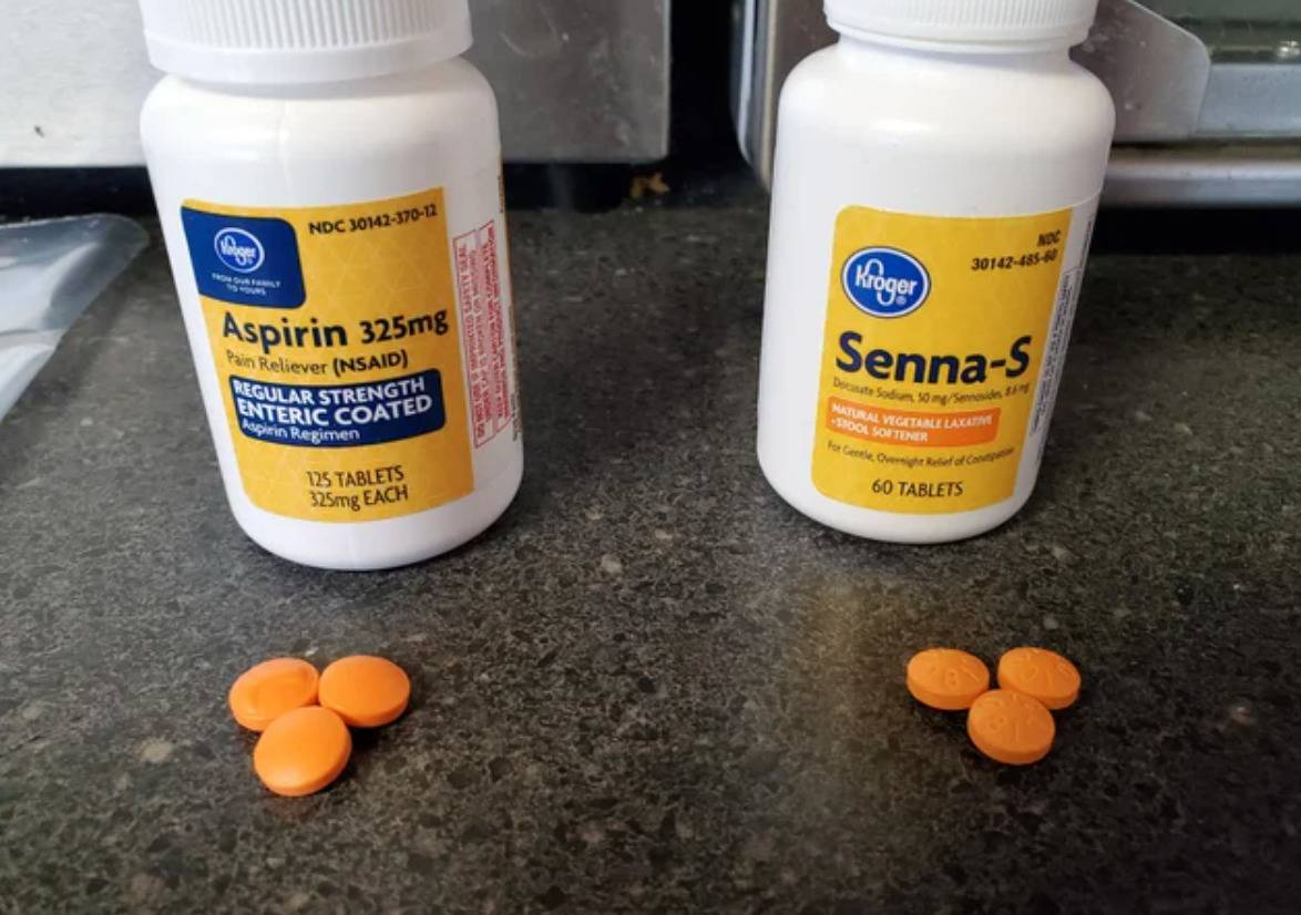 bottle of aspiring with orange pills and nearly identical bottle and pills, but it's a laxative