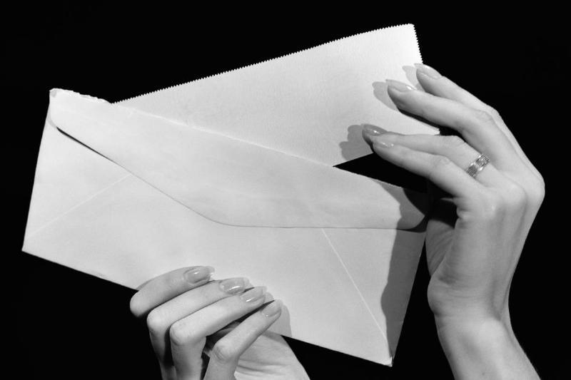 A woman slips a check into an envelope.