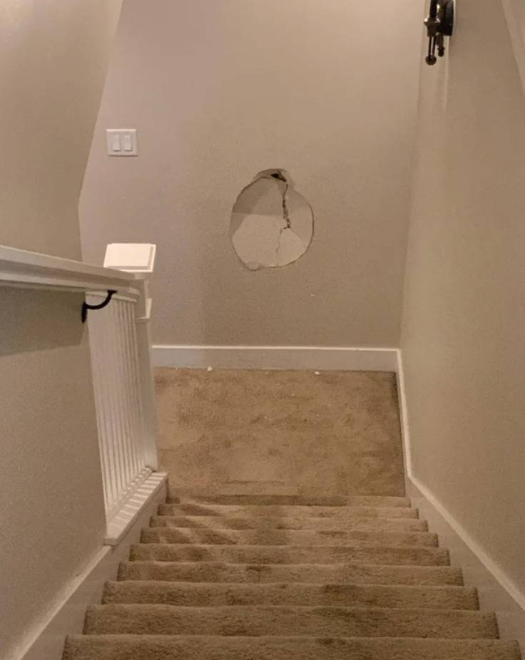 large hole in drywall at the bottom of a stairwell