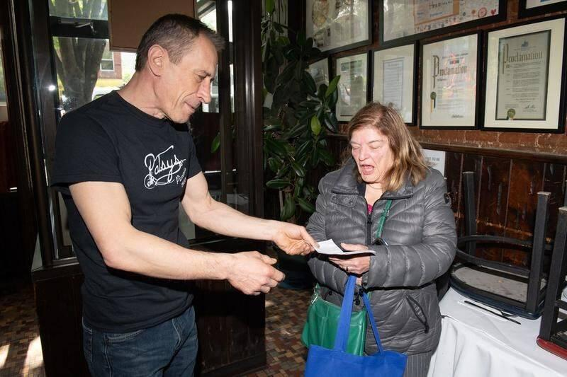 Brijac gives Vinacour her check.