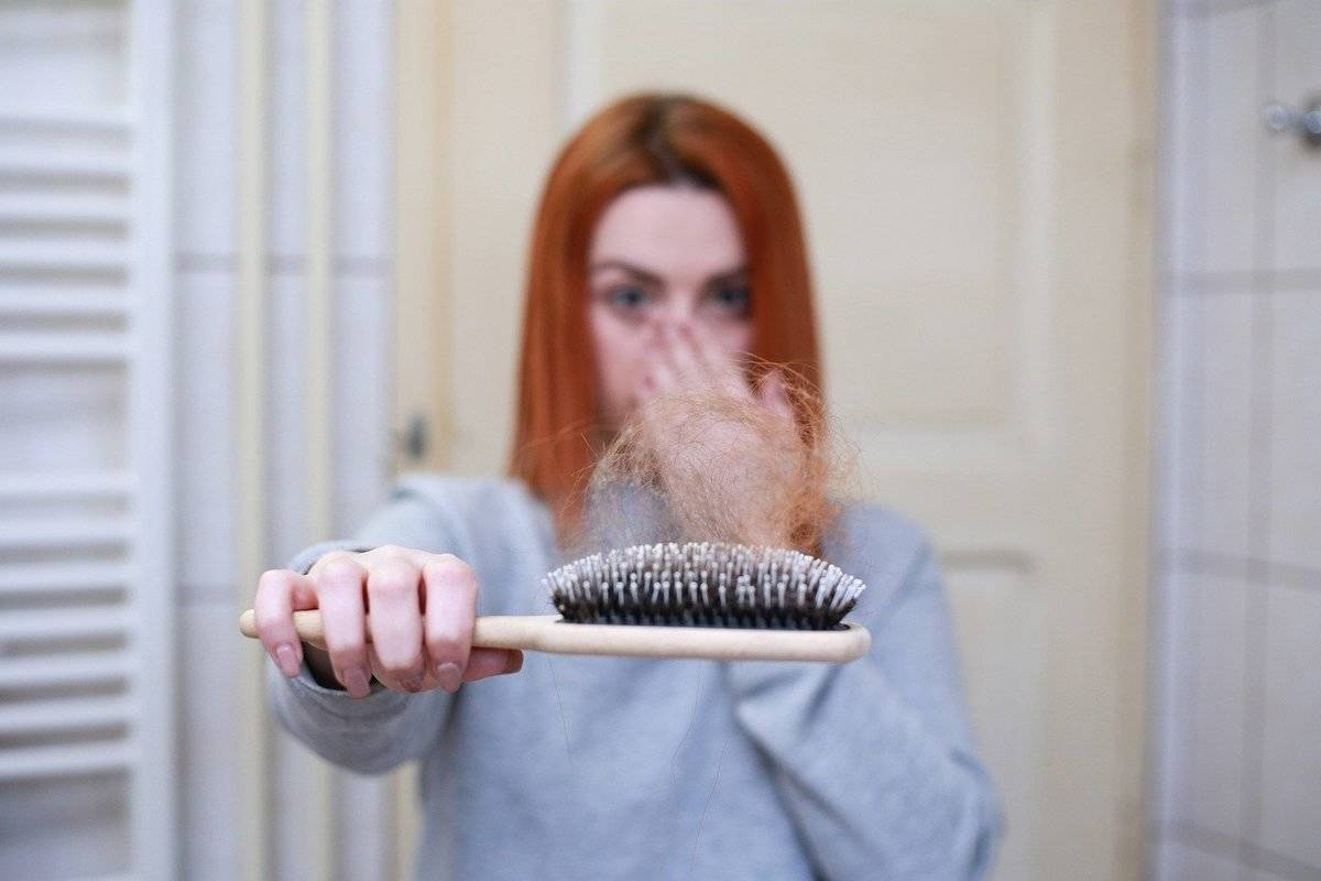 A woman holds out a brush with a lot of hair on it.