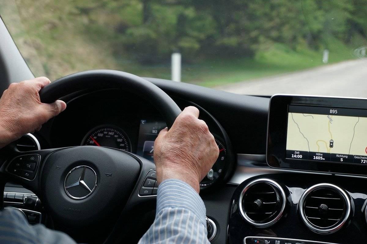 An elderly man drives a car.