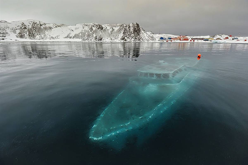 A yacht is frozen beneath a bay in Antarctica.