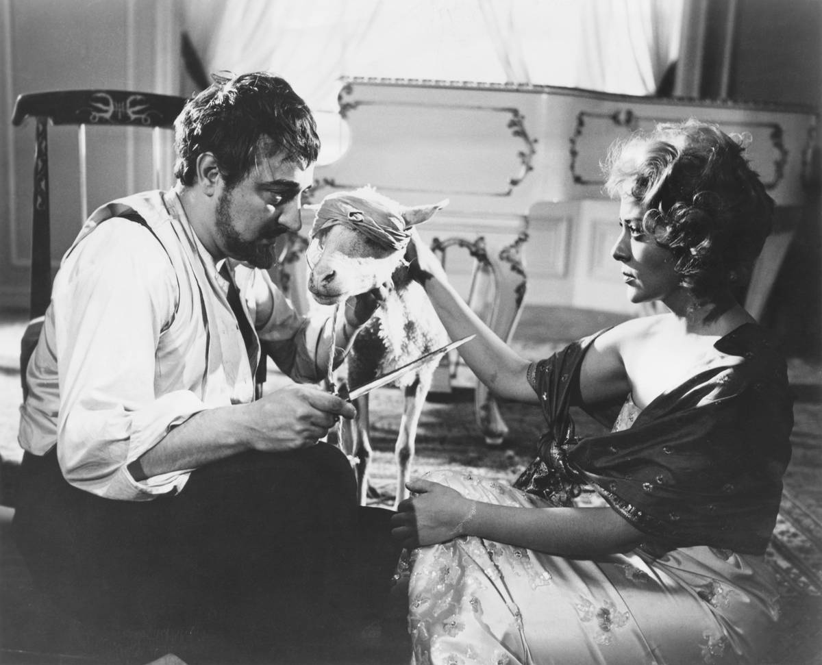 Dr. Comte (Augusto Benedico) and Leticia (Silvia Pinal) prepare to slaughter a goat in a scene from the 1962 film El Angel exterminador (The Exterminating Angel)