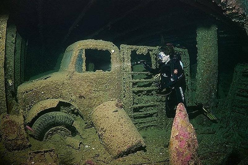 A diver swims by a vintage military truck from 1941.