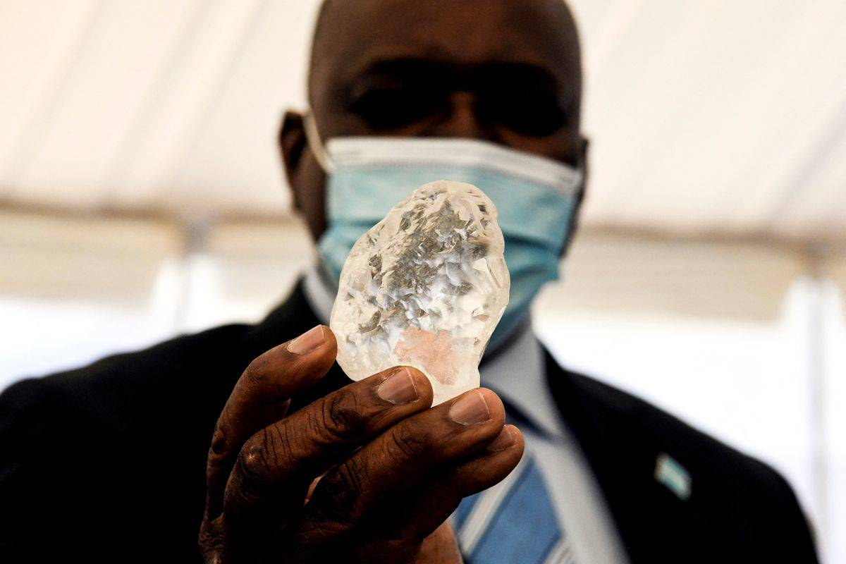 TOPSHOT - Botswana President Mokgweetsi Masisi (R) holds a gem diamond in Gaborone, Botswana, on June 16, 2021. - Botswanan diamond firm Debswana said on June 16, 2021 it had unearthed a 1,098-carat stone that it described as the third largest of its kind in the world. The stone, found on June 1, 2021 was shown to President Mokgweetsi Masisi in the capital Gaborone.