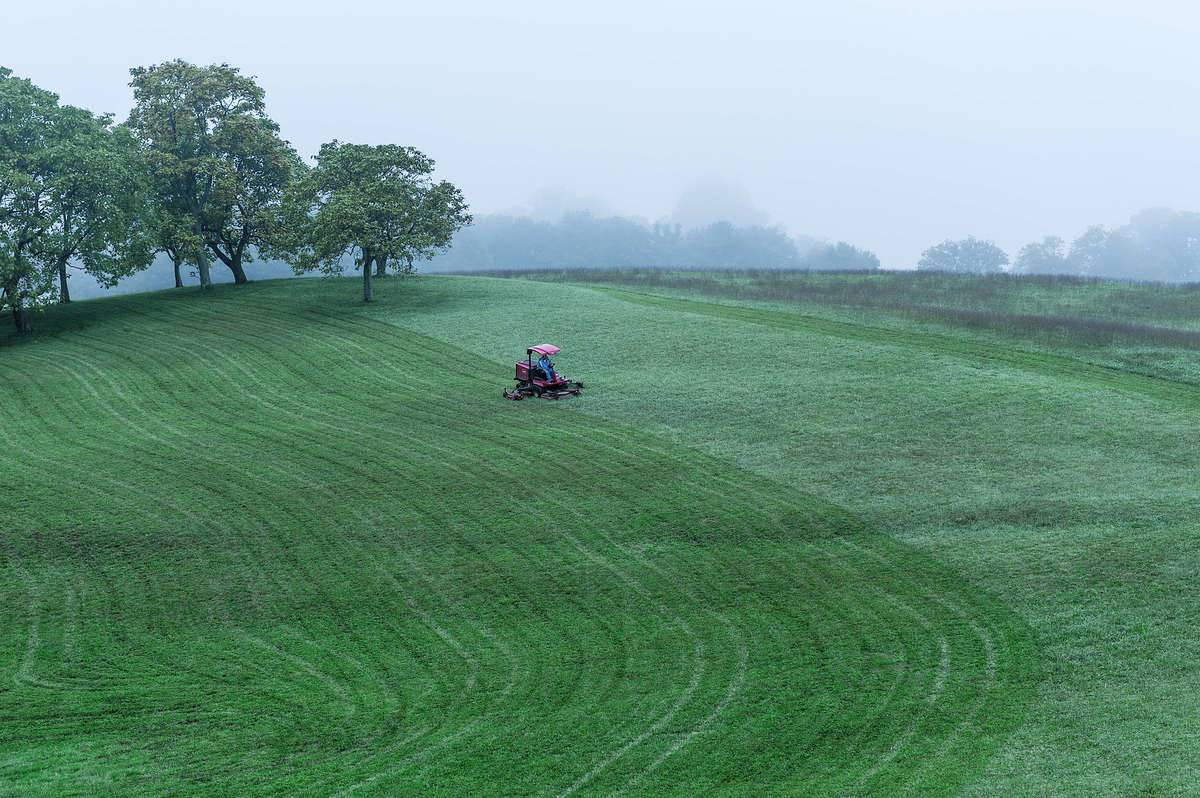Tractor mower cutting a large field of grass
