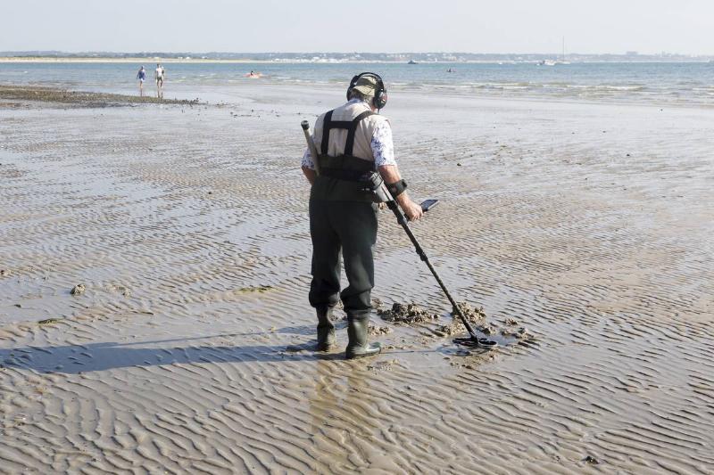 Male detectorist using metal detector at low tide, sandy beach Studland Bay, Swanage, Dorset, England, UK