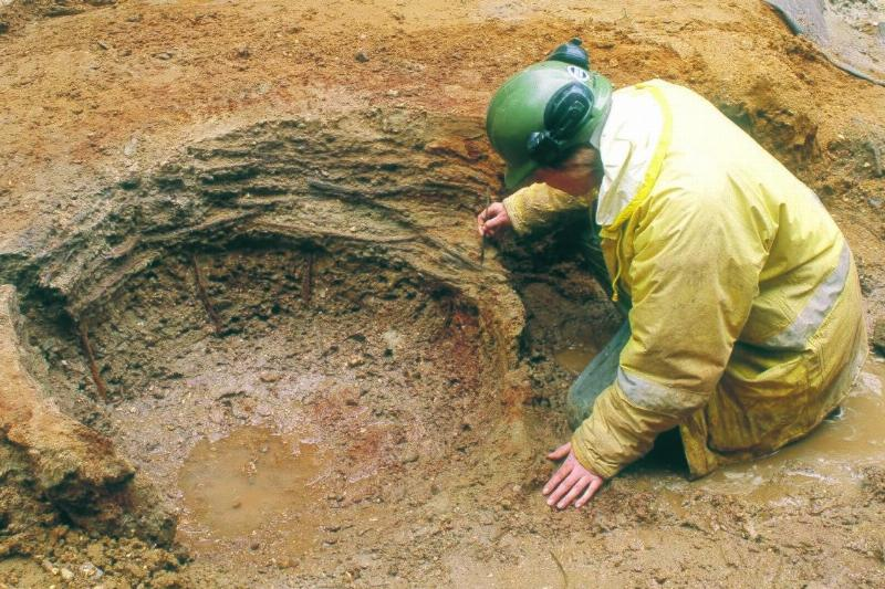 An archaeologist carefully excavating a construction pit lined with wattle which would have later been filled with a wooden barrel acting as a shaft for a well; from the excavation at 8–9 Long Acre, 26 August, 2005
