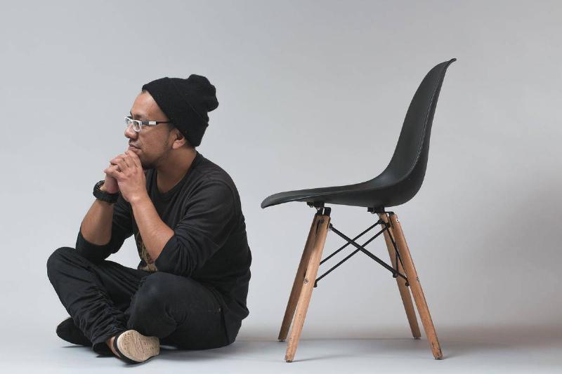 a man sitting cross-legged next to a chair