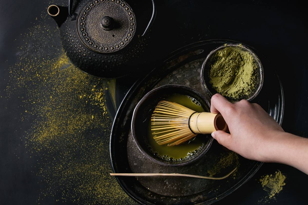 Green tea matcha powder and hot drink in black bowls standing with iron teapot, bamboo traditional tools spoon and whisk in hand in vintage tray over dark metal background