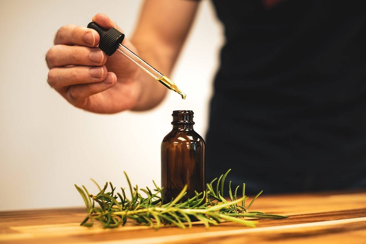 Taking_rosemary_oil_from_a_bottle