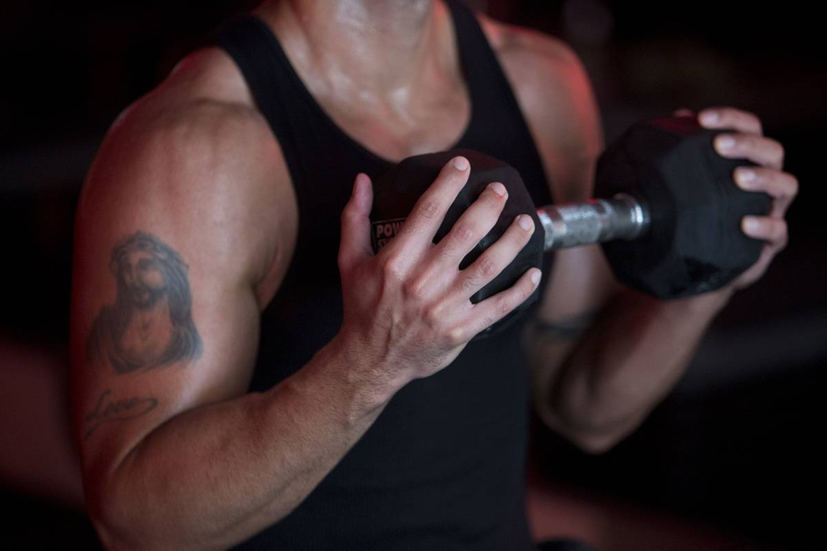 A client lifts a dumbbell in a
